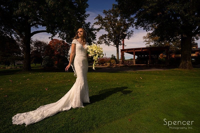 bride holding flowers in front of clubhouse at Firestone Country Club