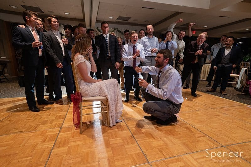 groom pulls out drink during garter removal at Firestone