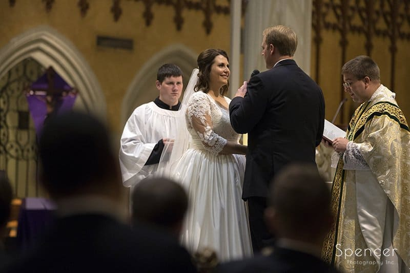 bride smiling at groom during wedding ceremony at Cathedral of St John the Evangelist
