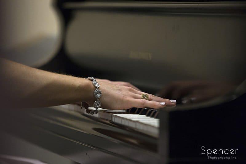 bridesmaids hands as she plays piano at Canton wedding