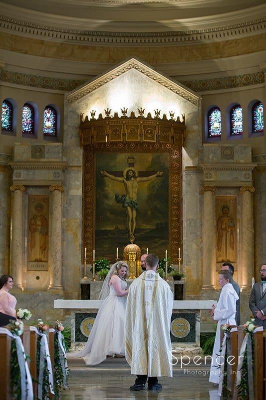 bride and groom on altar of Communion of Saints Parish