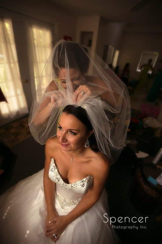bride putting on wedding veil at Country Cottage and Gardens