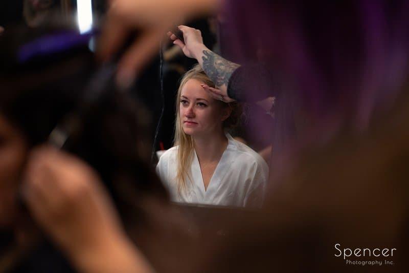 bride getting hair done on wedding day at Firestone
