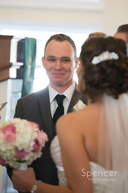 groom smiling at bride at wedding at Church on the Lakes