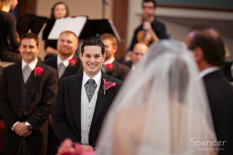groom watching bride walk down aisle at wedding ceremony at Cornerstone Church Medina
