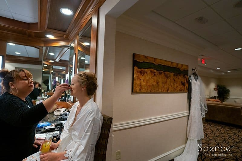 bride getting make up on wedding day at Firestone Country Club