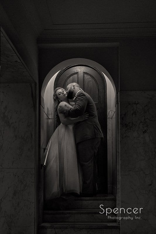 beautiful black and white wedding picture of groom kissing bride at Communion of Saints Parish
