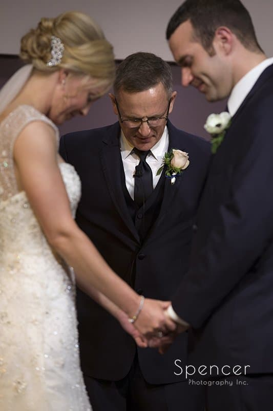 bride and groom holding hands at wedding ceremony at Canton Baptist Temple