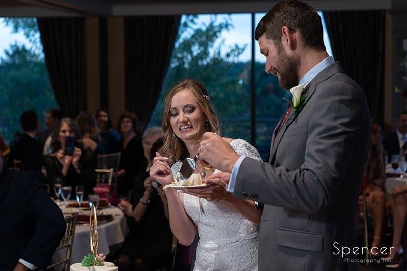 groom feeding bride wedding cake at Firestone Country Club