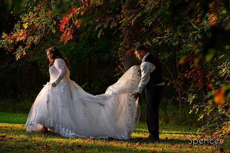 groom helping bride with wedding dress after her fall wedding