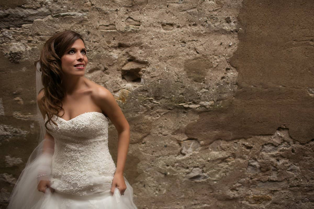 Bride holding wedding dress in front of concrete wall at wedding in Sandusky Ohio