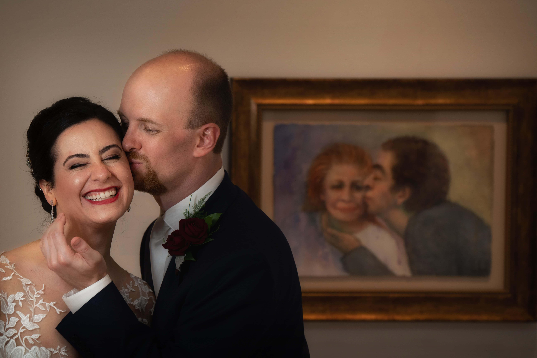Groom kissing bride on cheek at Butler Museum of Art