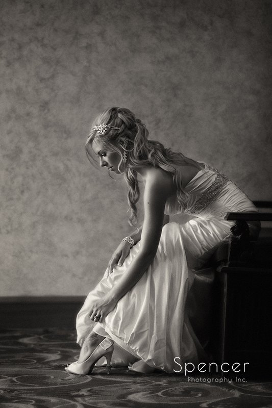 bride adjusting her shoe in wedding pictures in Akron Civic Theater