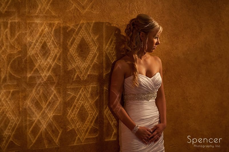 bride leaning up against wall in wedding pictures at Akron Civic Theater