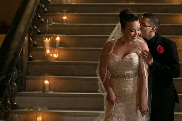 groom kissing bride on cheek on staircase at Cleveland Union Club