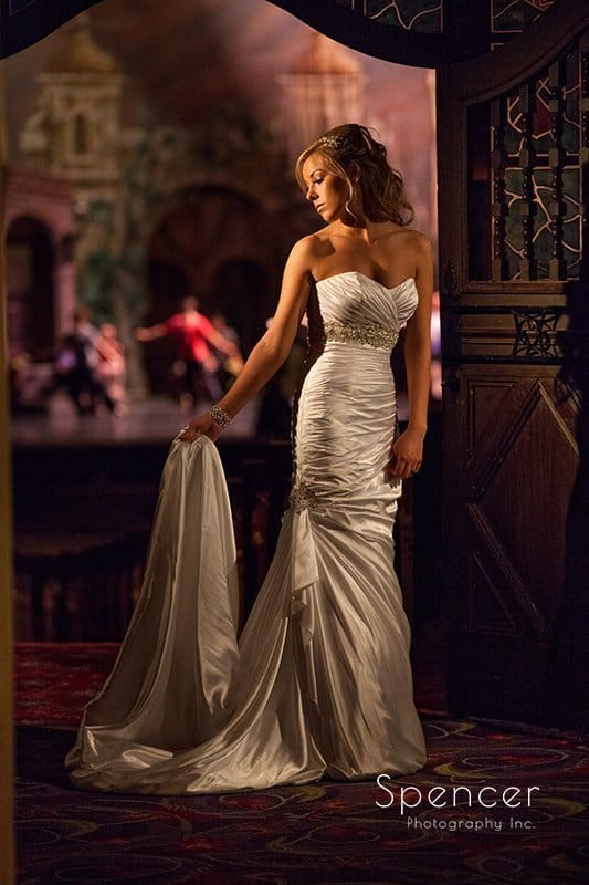 wedding picture of bride holding her dress in front of Akron Civic Theater