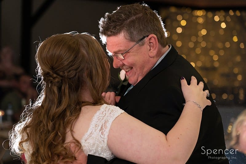 father smiling at bride while dancing