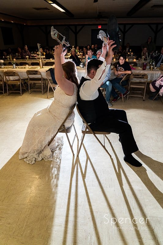 bride and groom play shoe game at wedding reception
