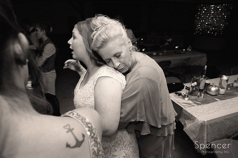 mom hugging bride at wedding reception