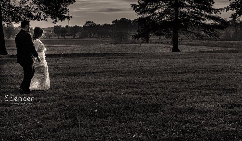 sepia picture of bride and groom walking at sunset