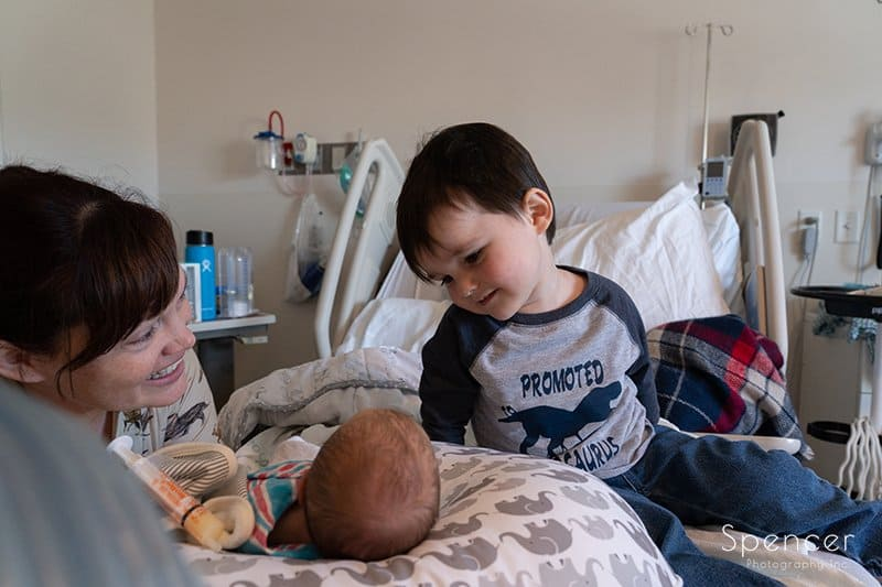 toddler sees little brother and smiles
