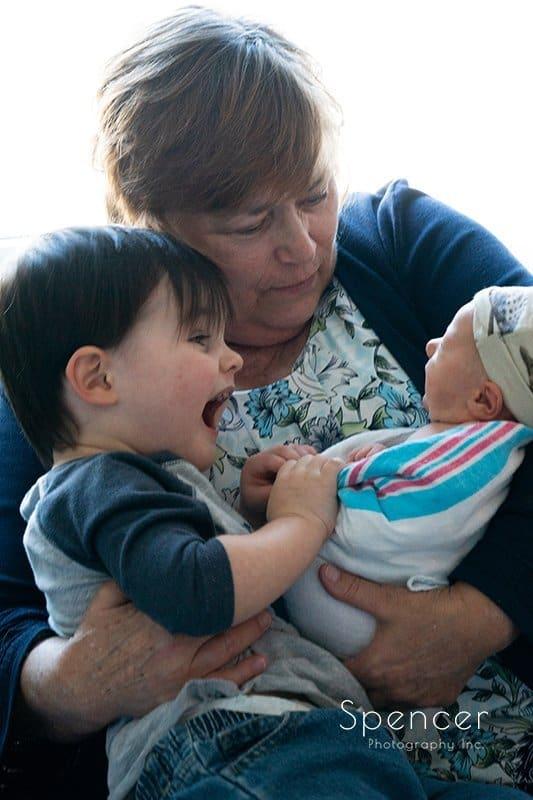 toddler and grandma with newborn baby