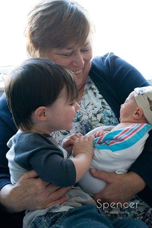 grandma and toddler holding newborn