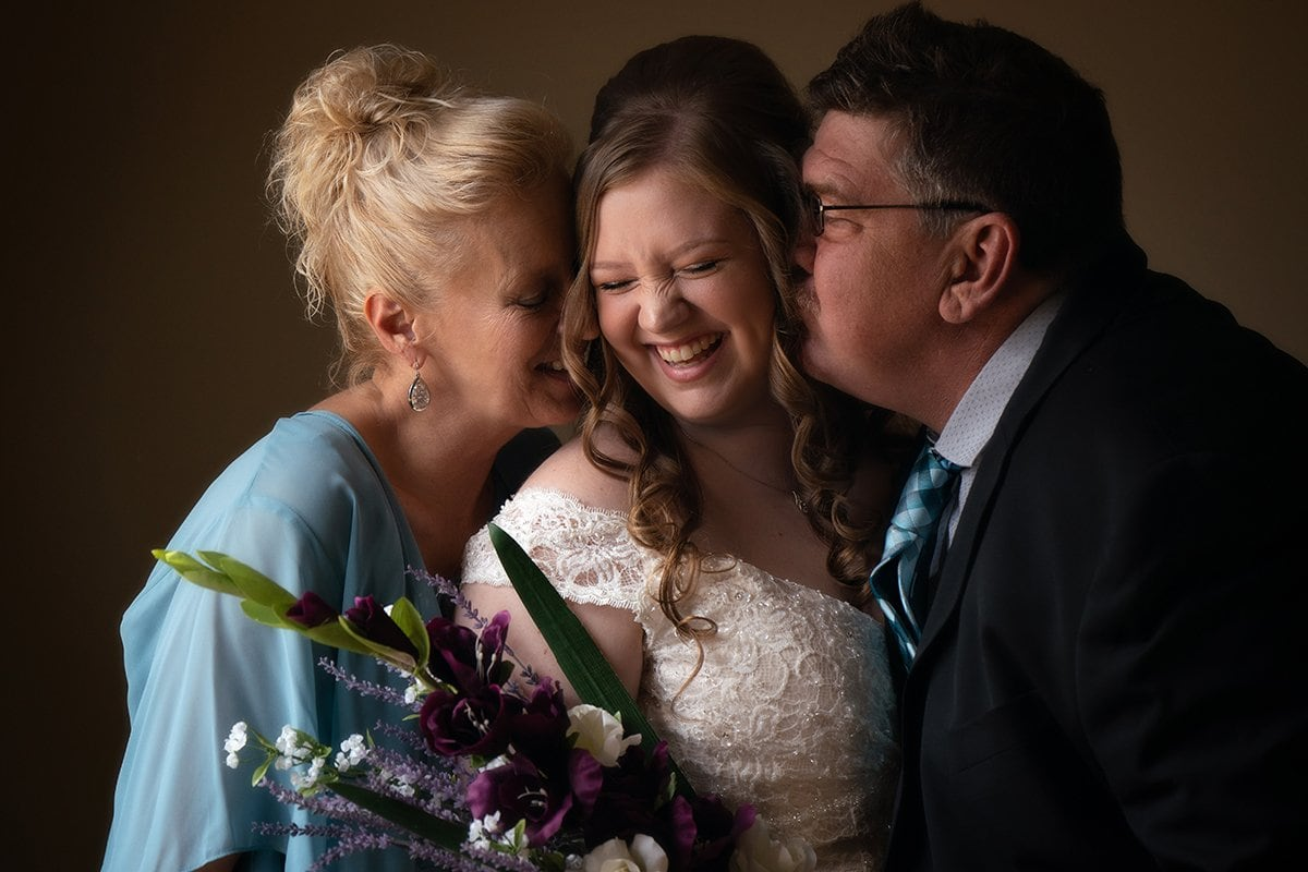 Cleveland bride laughing as parents kiss her