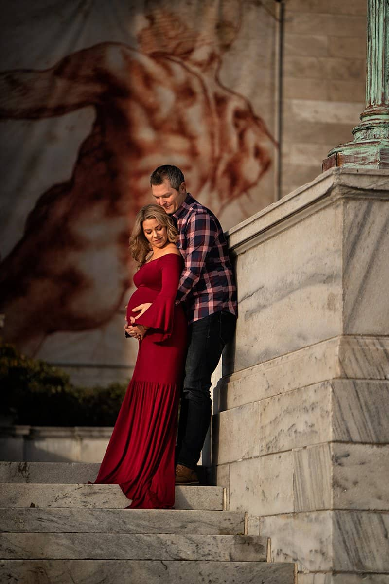new parents posing for maternity picture in front of Cleveland Museum of Art