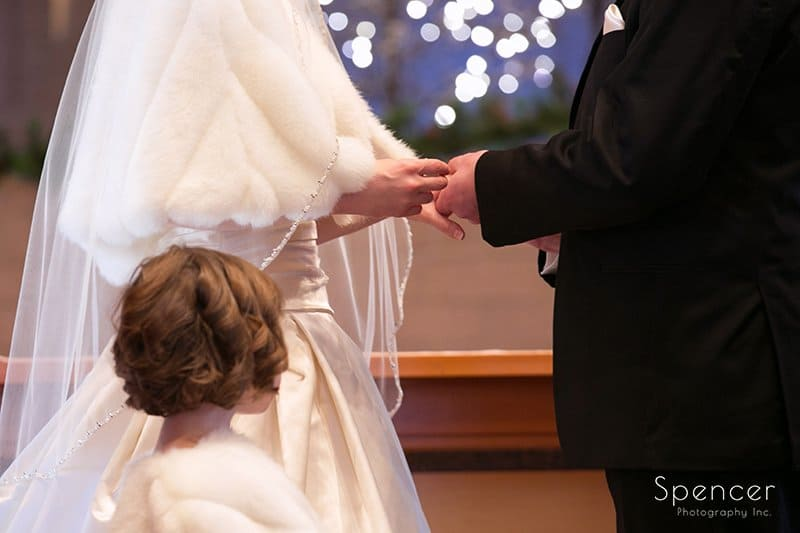 bride putting on wedding ring at Christmas wedding at Holy Angels