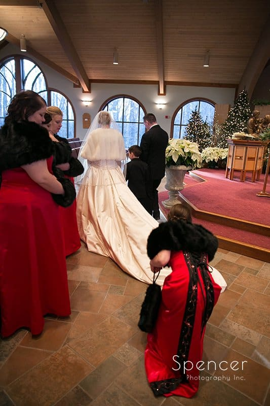 bridesmaid helping bride with dress at Holy Angels Chruch