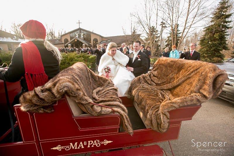 bride and groom getting into Chrismas sleigh
