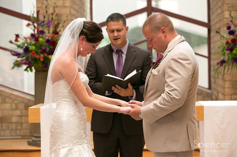 bride and groom praying during wedding ceremony at Montrose Zion Church