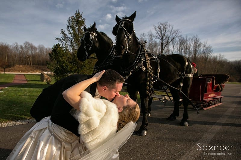 groom kissing bride after Christmas wedding at Holy Angels