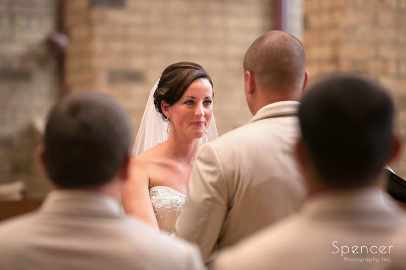 bride smiling at groom during wedding ceremony at Montrose Zion Church