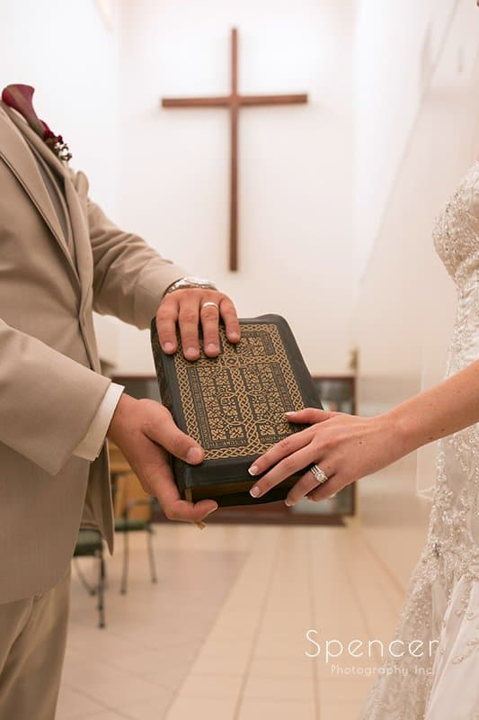 bride and groom holding bible at Montrose Zion Church wedding ceremony