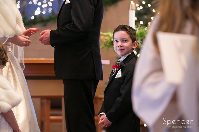 ring bearer smiling at camera during Holy Angels wedding ceremony