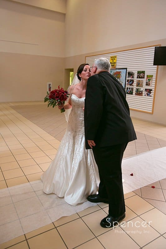 dad kisses bride before wedding ceremony at Montrose Zion Church