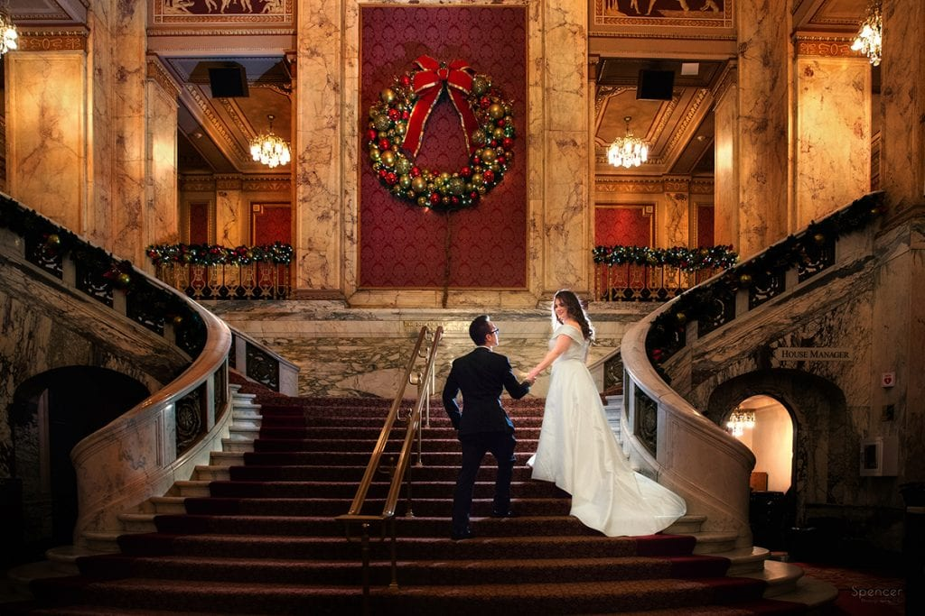 Christmas wedding picture of groom holding brides hand at Playhouse Square Cleveland