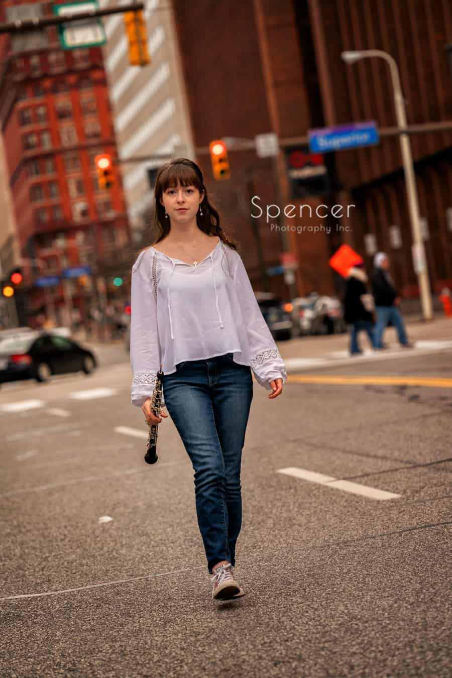 senior portrait of girl with oboe walking down Cleveland street