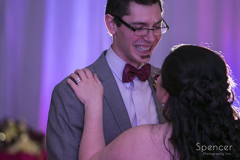 groom smiles at bride during first dance