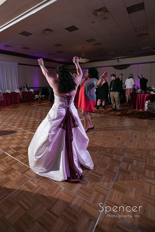 bride lifts arms up on dancefloor of Cleveland Marriott