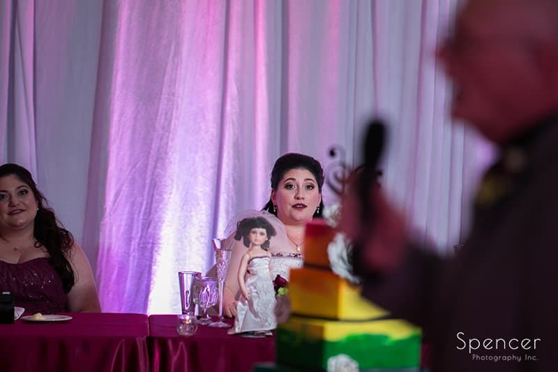 bride watching father give reception speech