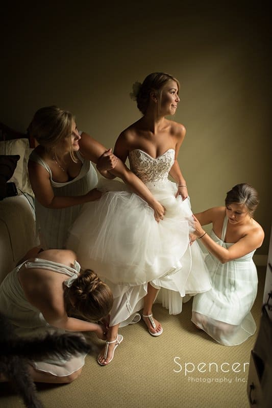 bride laughing while putting her wedding dress