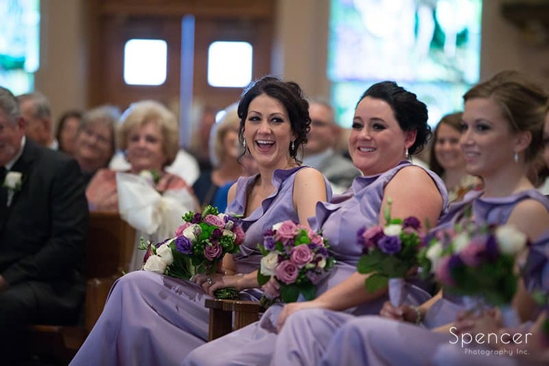bridesmaids laugh during wedding at St. Paul's Catholic Church