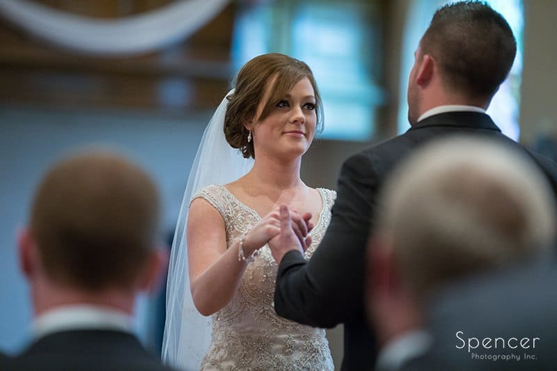 bride and groom hold hands during wedding at St. Paul's