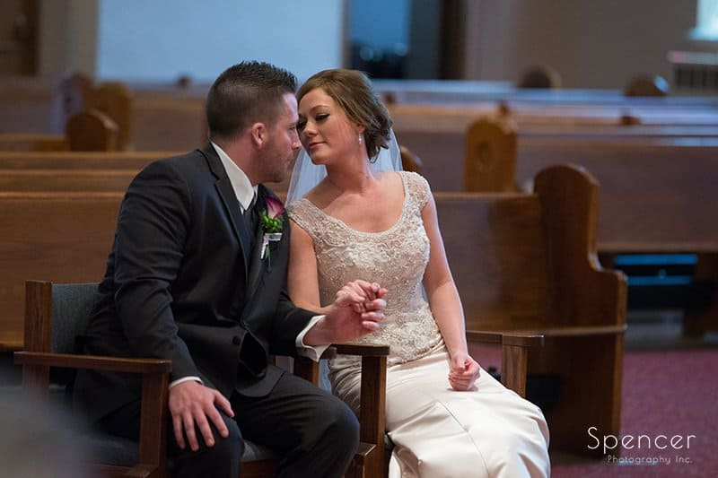bride and groom kissing during wedding at St. Paul's Catholic chruch