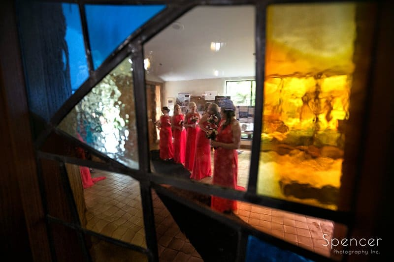 bridesmaids through stained glass at St. Barnabas