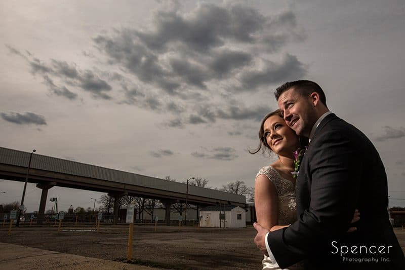 dramatic picture of bride and groom under cloudy sky in akron