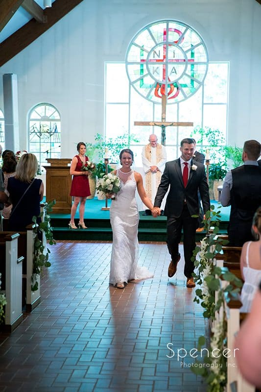 bride and groom walking down aisle at Divine Word Church